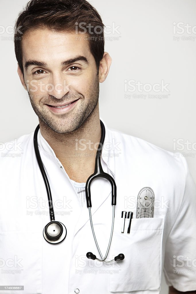 Portrait of mid adult doctor wearing stethoscope against white background royalty-free stock photo