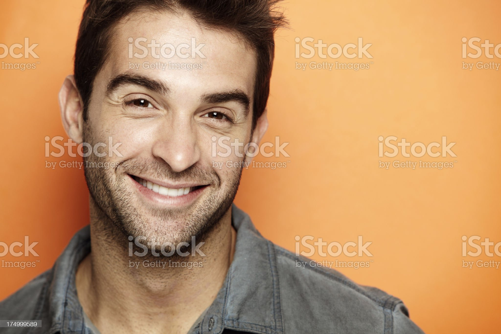 Portrait of mid adult man smiling against orange background royalty-free stock photo