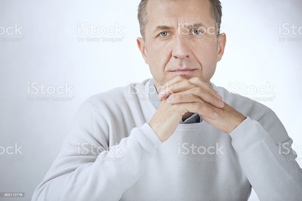Portrait of middle aged serious businessman sitting with hands stock photo