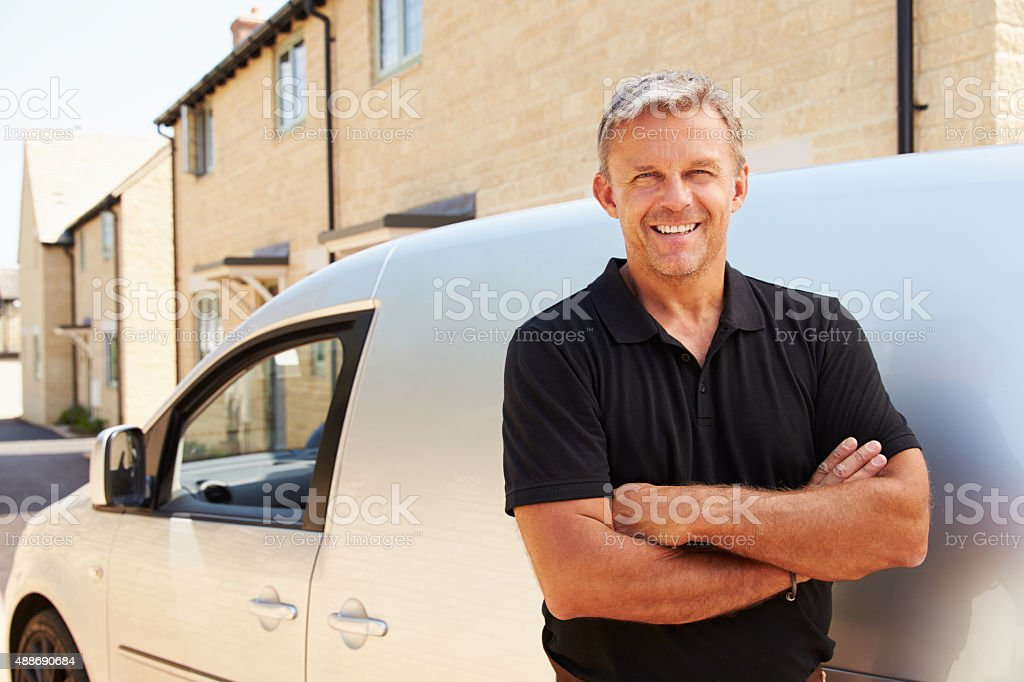 Portrait of middle aged tradesman standing by his van stock photo