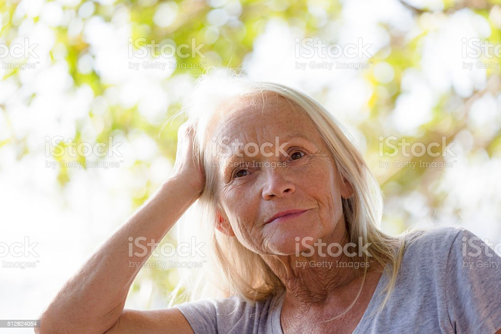 Portrait of modern attractive mature woman with long blond hair stock photo