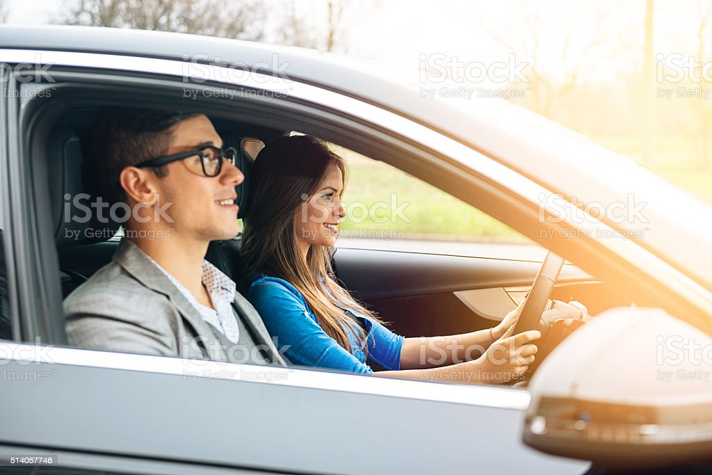 Portrait of modern young couple driving luxury car to vacation stock photo