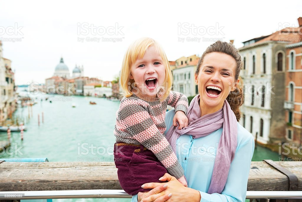 Portrait of mother and baby on bridge in venice, italy stock photo