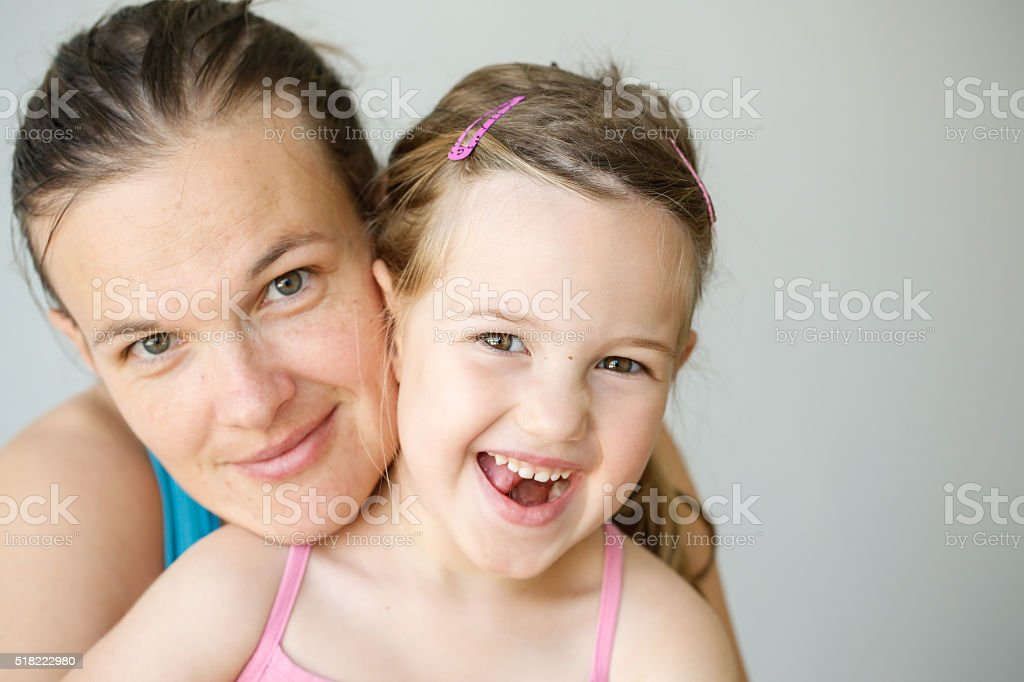 Portrait of mother and daughter embracing, smiling stock photo