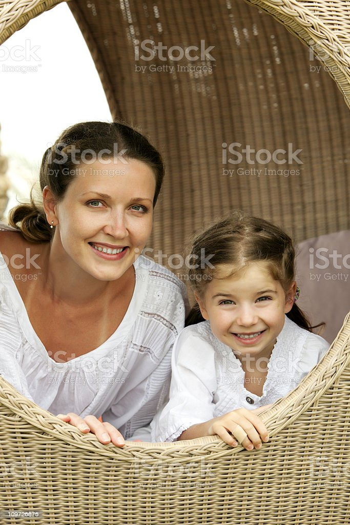 Portrait of mother and daughter sitting in beach pod royalty-free stock photo