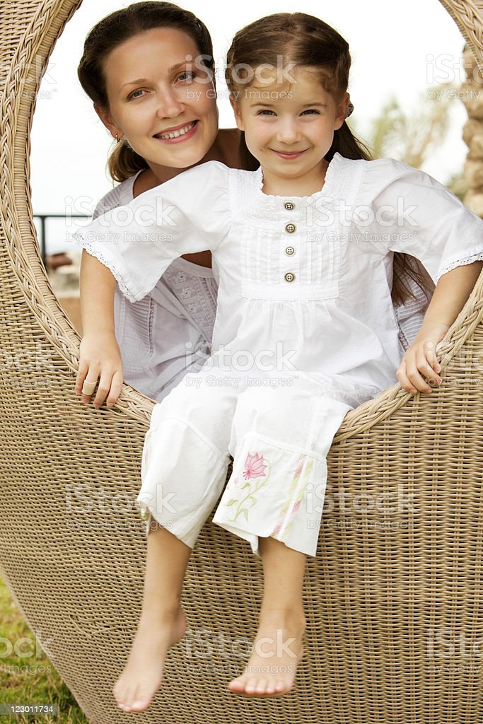 Portrait of mother and daughter sitting in beach pod stock photo