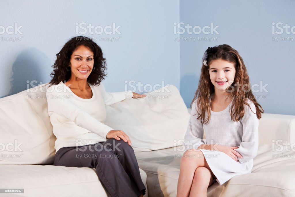 Portrait of mother and daughter sitting on sofa stock photo