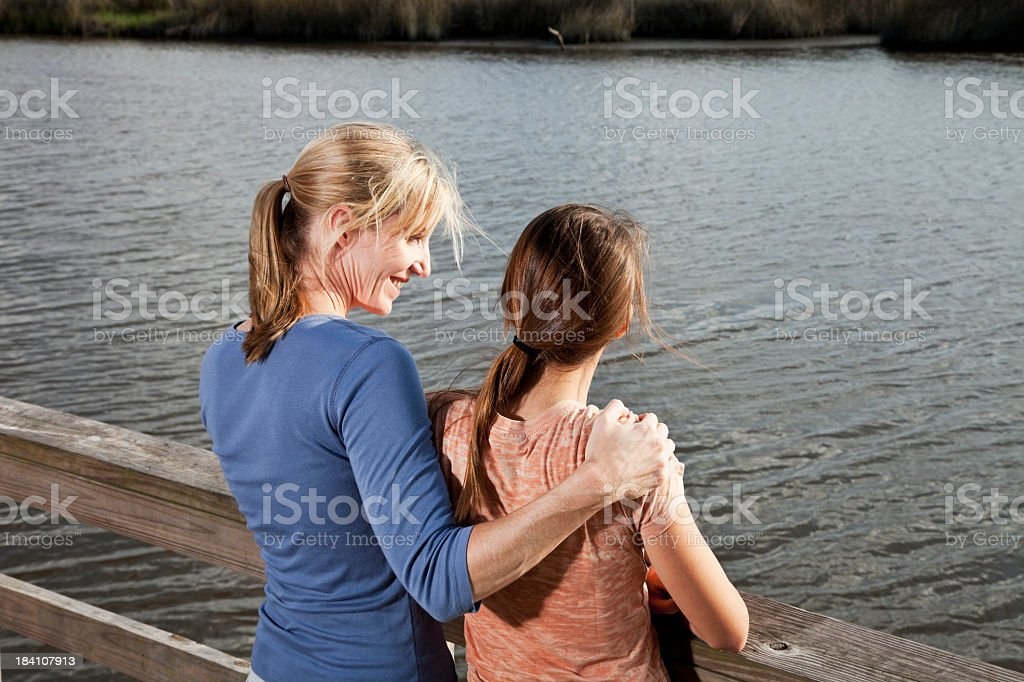 Portrait of mother and teen daughter outdoors by water stock photo