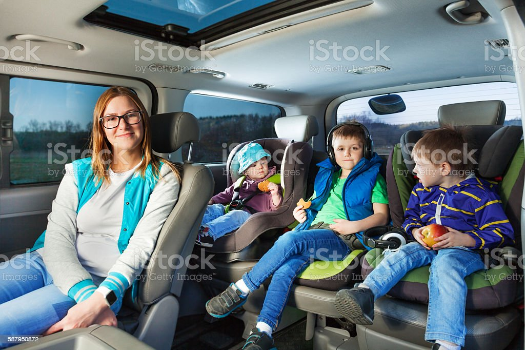 Portrait of mother and three boys sitting in a car stock photo
