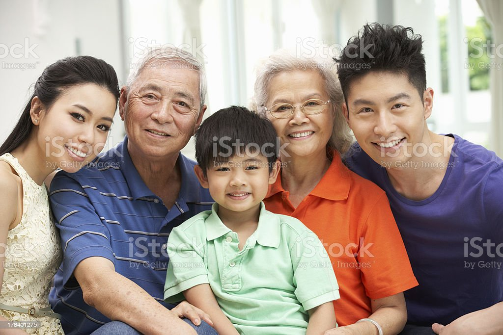 Portrait Of Multi-Generation Chinese Family Relaxing At Home Tog stock photo