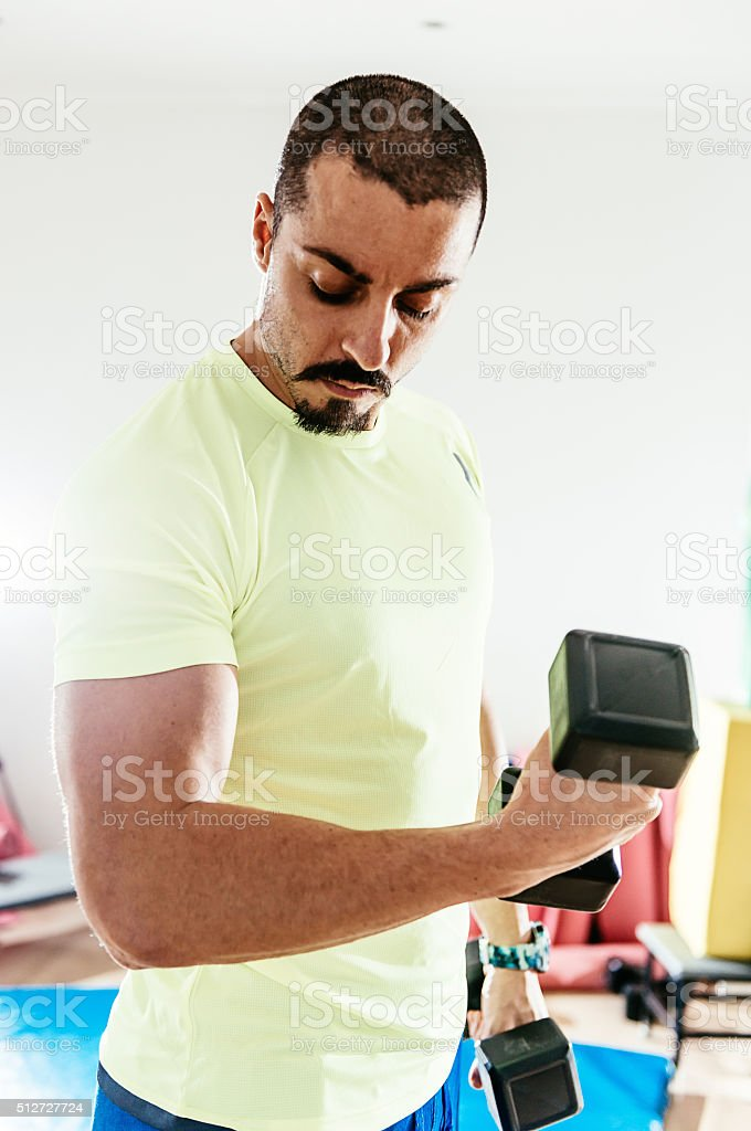 Portrait of muscular male caucasian exercising biceps stock photo