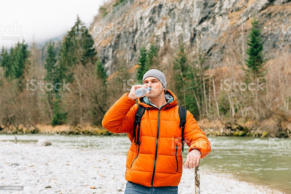 Portrait of nature hiker drinking water and heading towards river stock photo