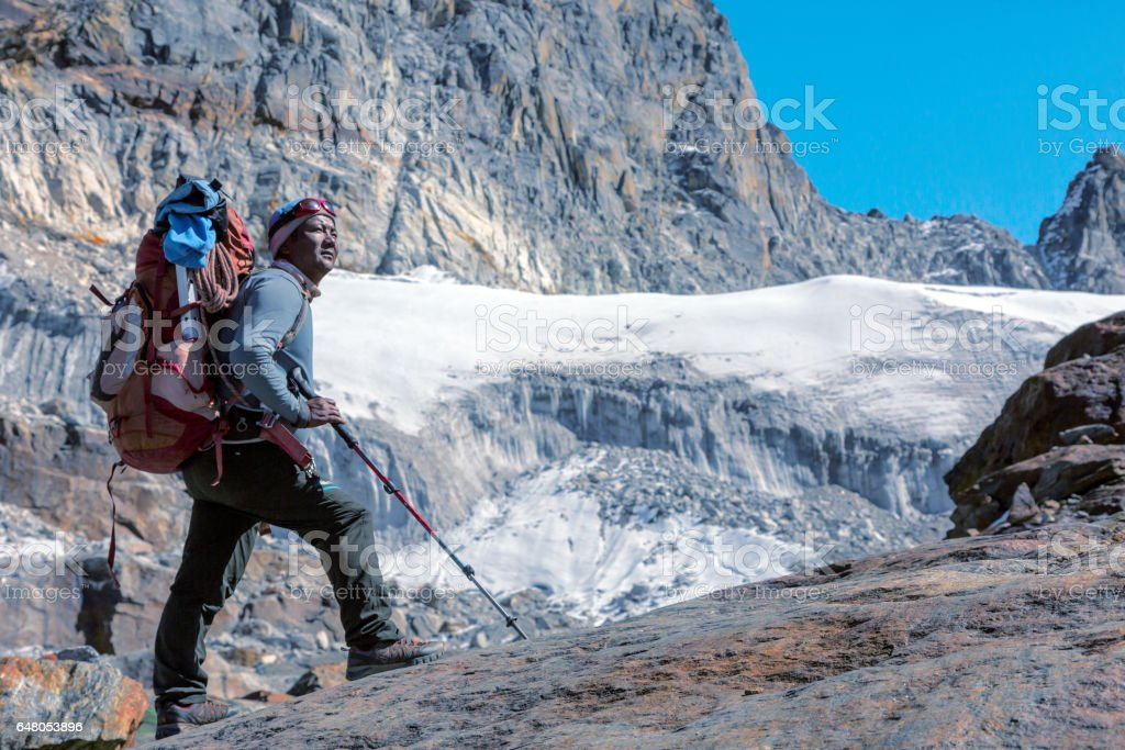 Portrait of Nepalese Mountain Guide staying on Glacier toned stock photo