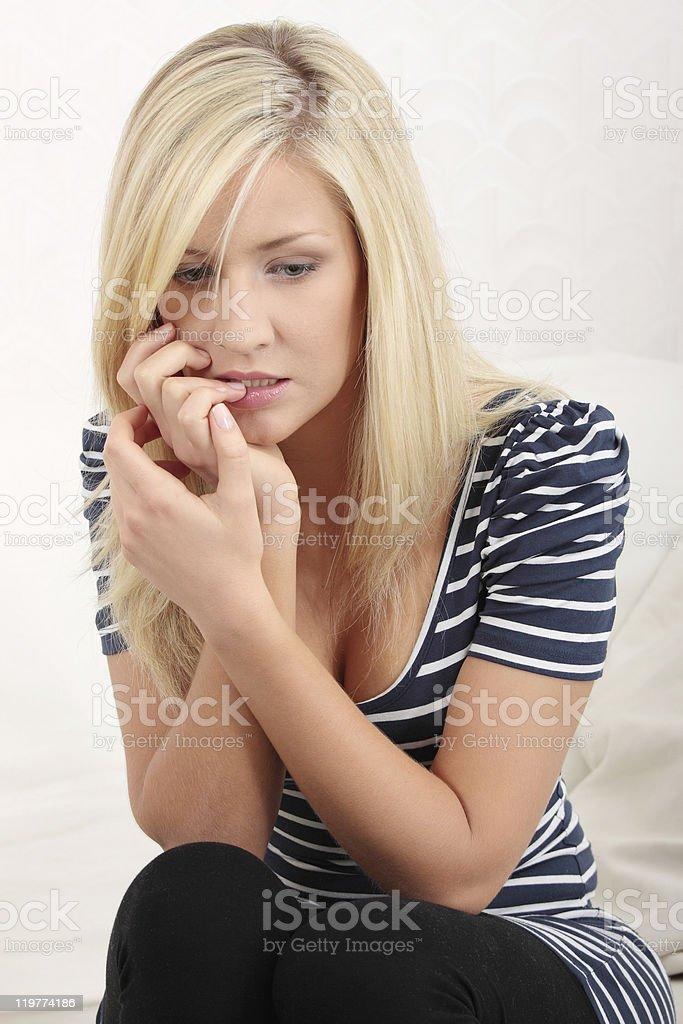 Portrait of nervous blonde girl biting nails stock photo