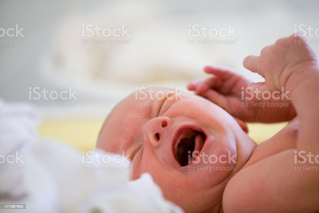 Portrait of newborn baby crying in bed stock photo