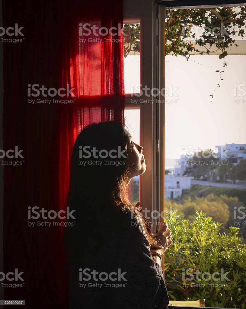 portrait of nice young woman looks out window royalty-free stock photo