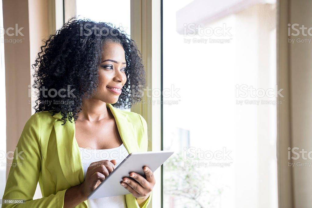 Portrait of Nigerian woman looking through window with tablet stock photo