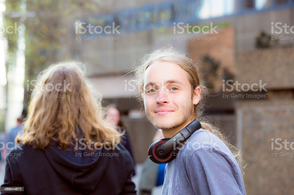 Portrait of nineteen years old teenage boy with headphones, outdoor stock photo
