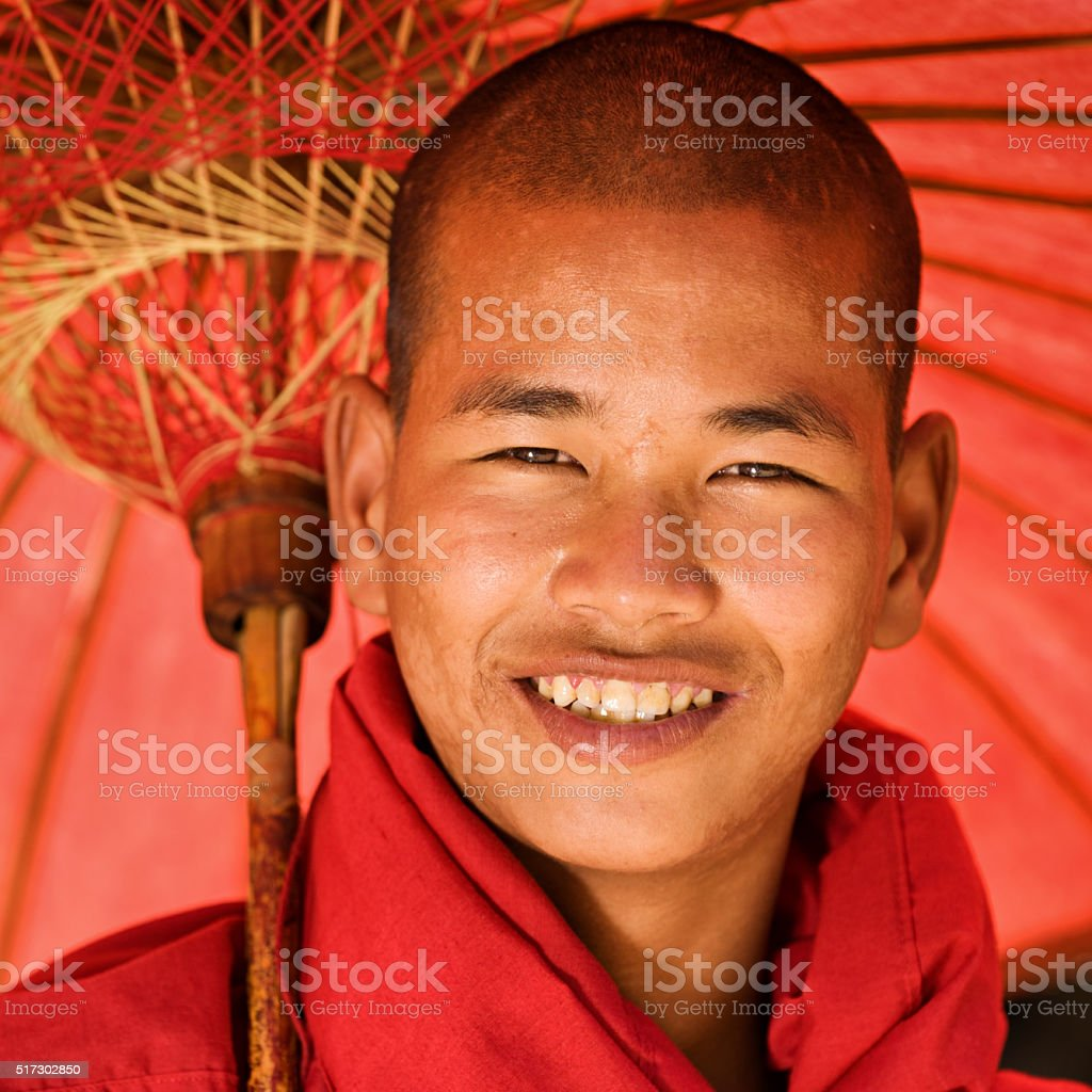 Portrait of Novice Buddhist monk with umbrella stock photo
