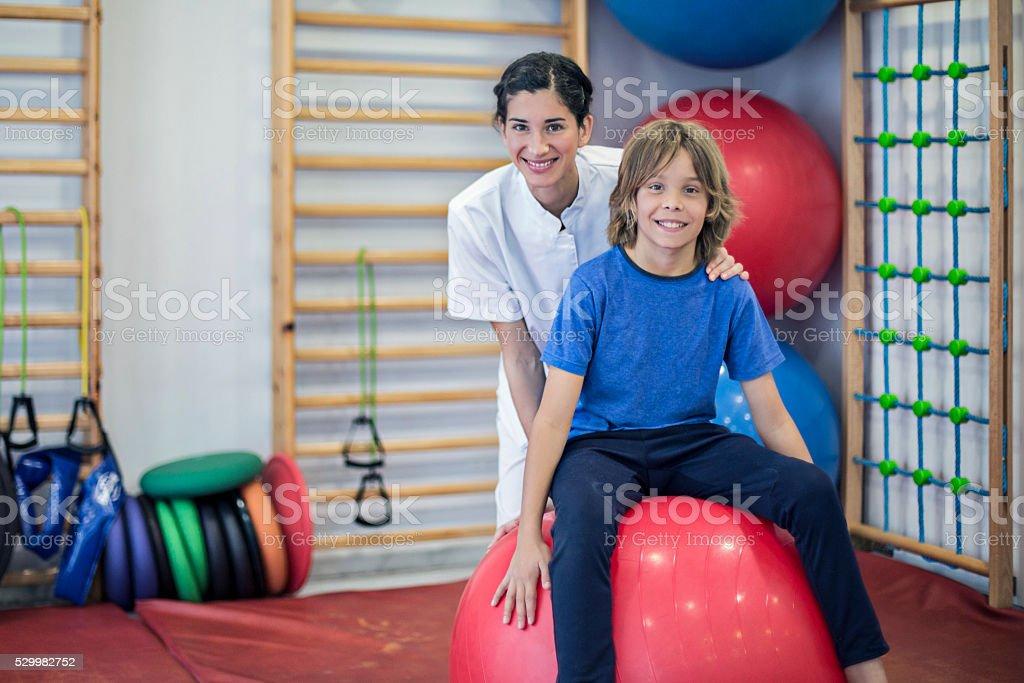Portrait of nurse and child doing rehabilitation stock photo