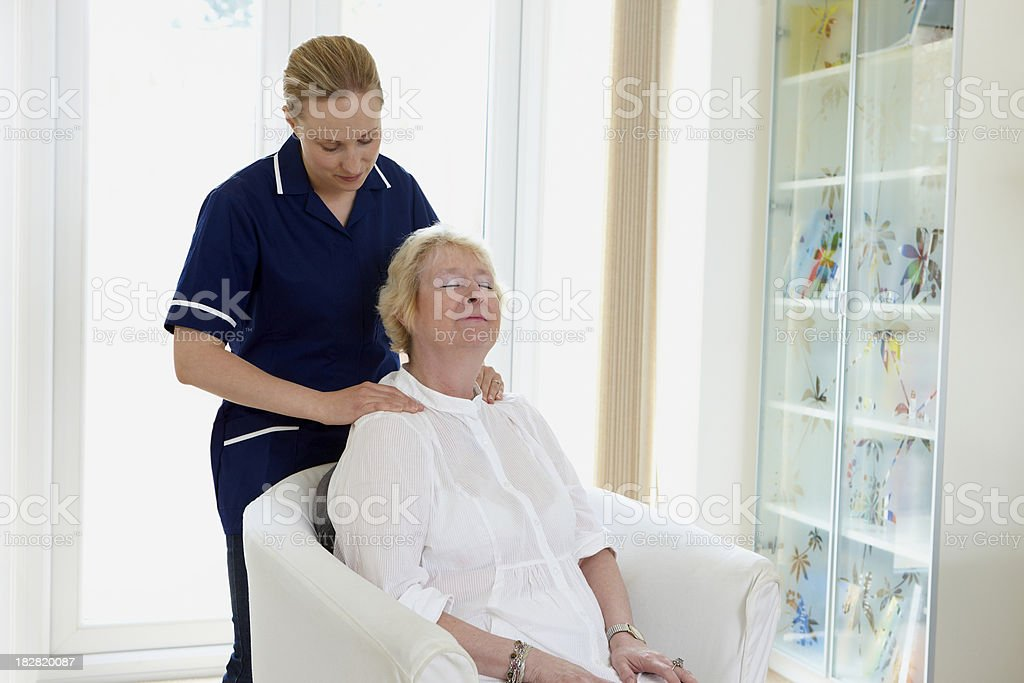 portrait of nurse massaging senior woman royalty-free stock photo