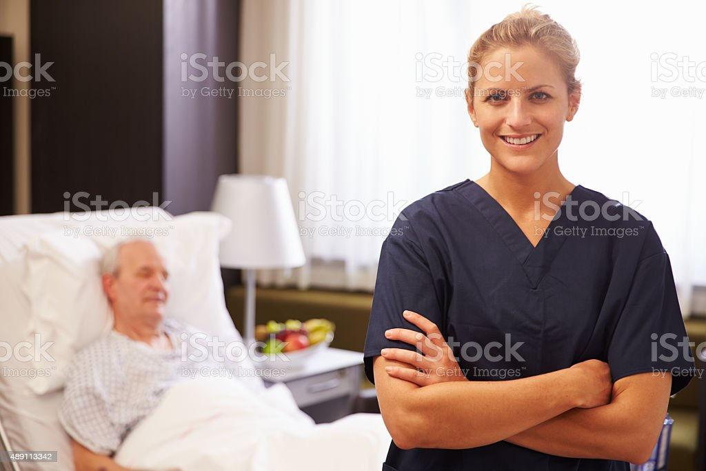 Portrait Of Nurse With Senior Male Patient In Hospital Bed stock photo