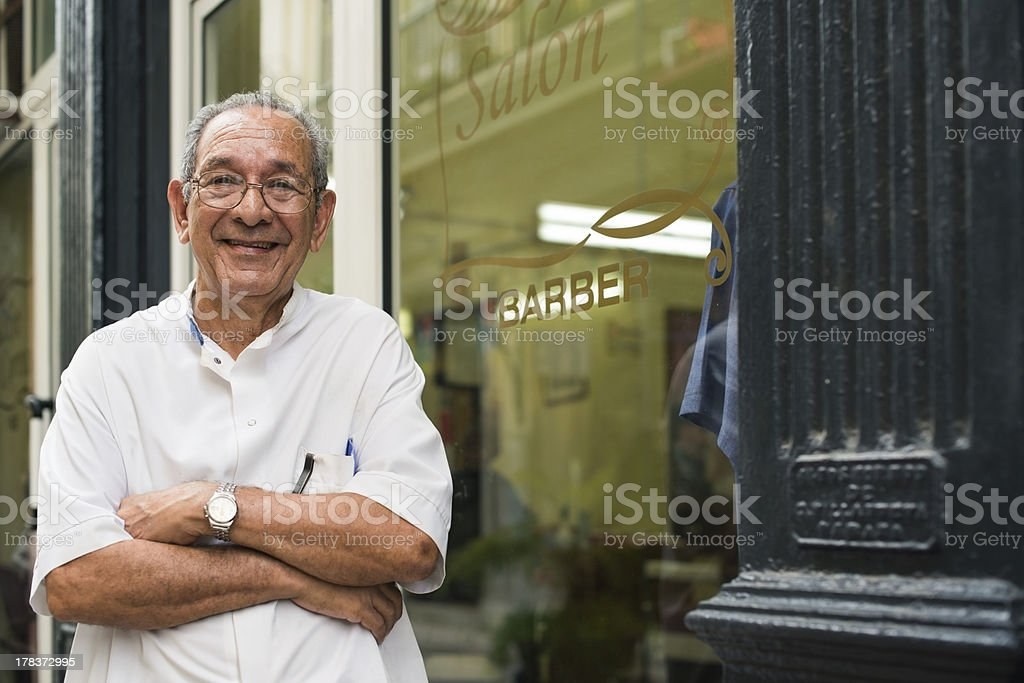 portrait of old barber smiling in hair salon stock photo