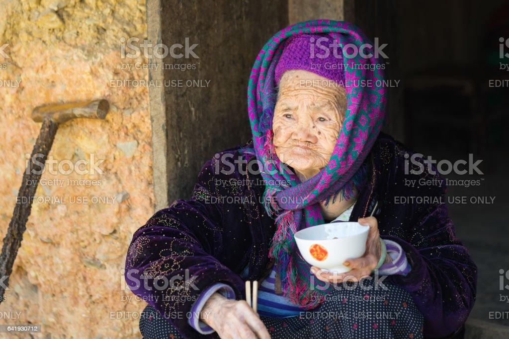 Ha Giang, Vietnam - Feb 14, 2016: Portrait of old Hmong woman having meal on door step in Dong Van district stock photo