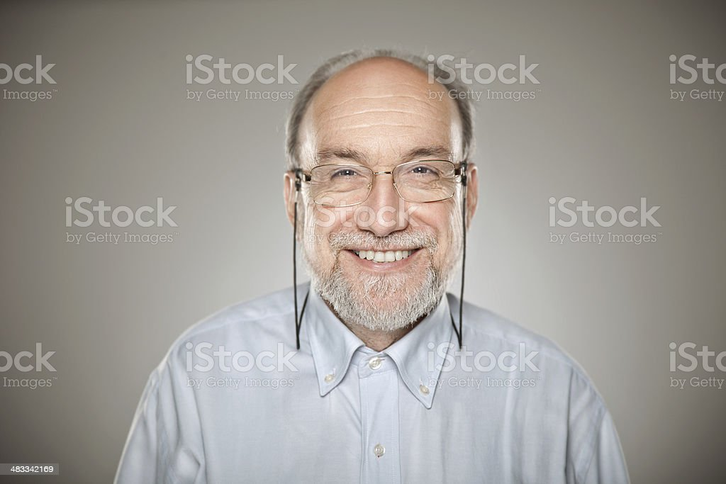 Portrait of old man taking glasses and smiling stock photo