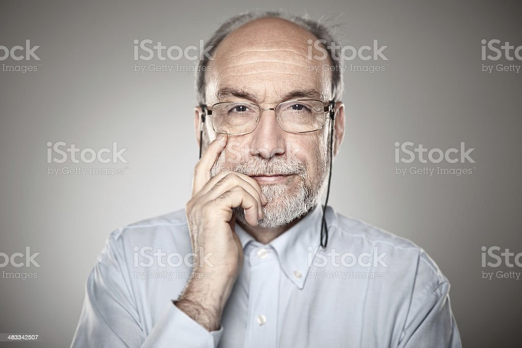 Portrait of old man taking glasses stock photo