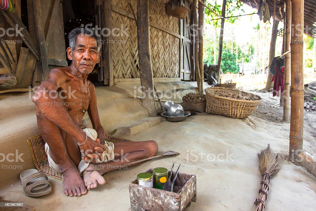 Portrait of old tribal man sitting in his hut stock photo
