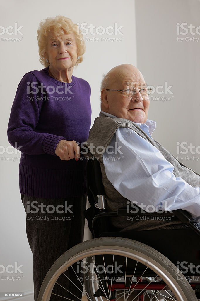 Portrait of old woman with her husband in a wheelchair royalty-free stock photo