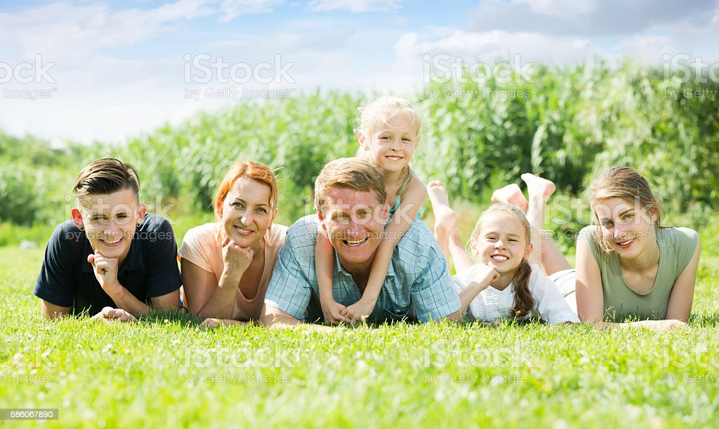 Portrait of ordinary large family lying on green lawn outdoors stock photo