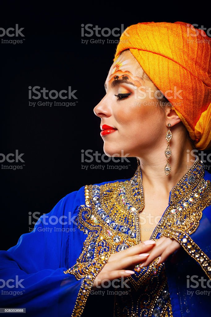 Portrait of oriental beauty in a turban and face art. stock photo