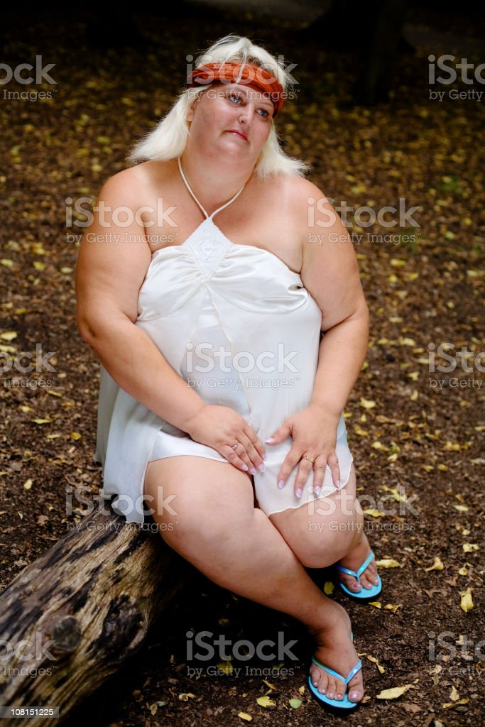 Portrait of Overweight Woman Sitting on Log in Forest royalty-free stock photo