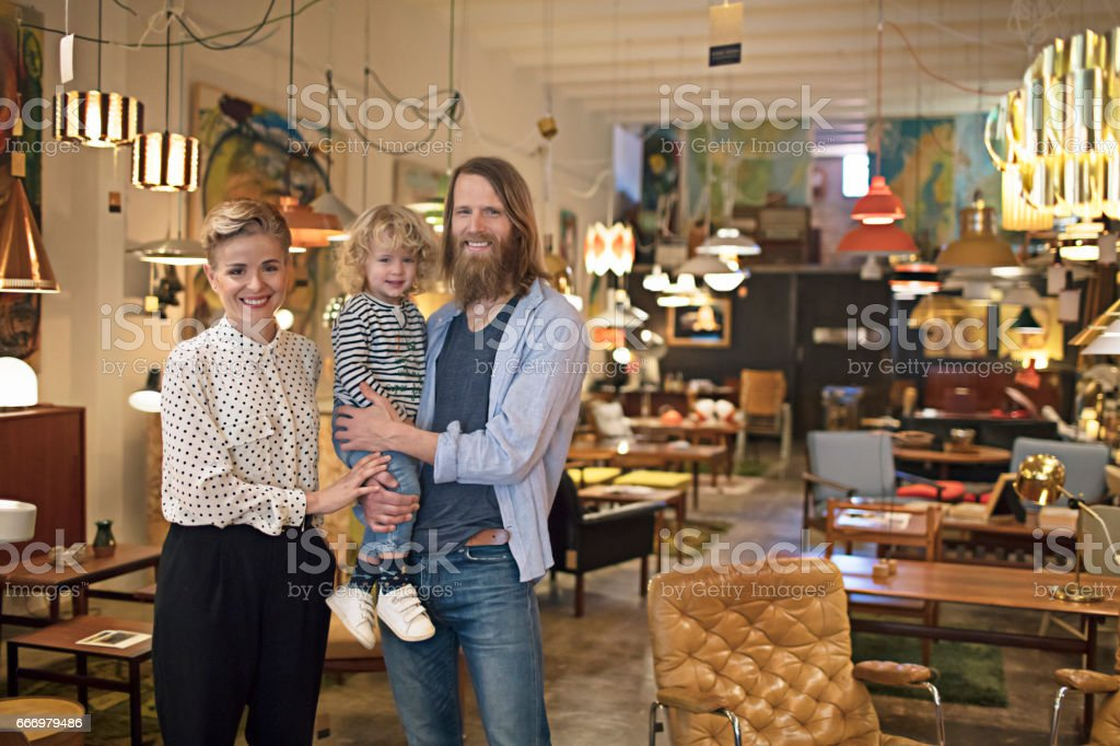 Portrait of owners with son at furniture shop stock photo