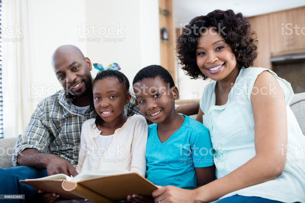 Portrait of parents and their children looking at photo album in living room stock photo