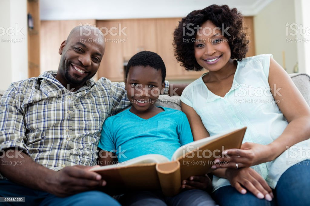 Portrait of parents and their son looking at photo album in living room stock photo