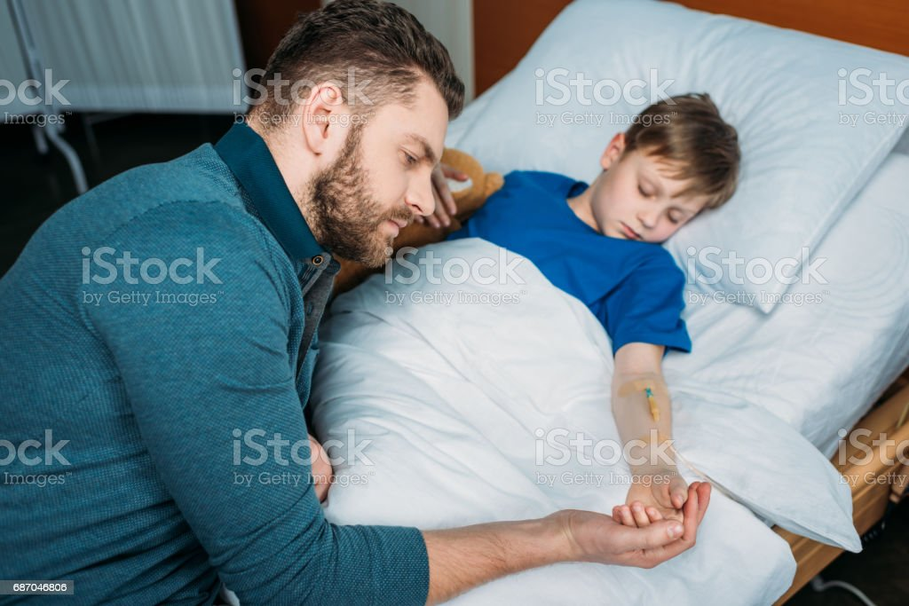 portrait of pensive dad sitting near sick son in hospital bed stock photo