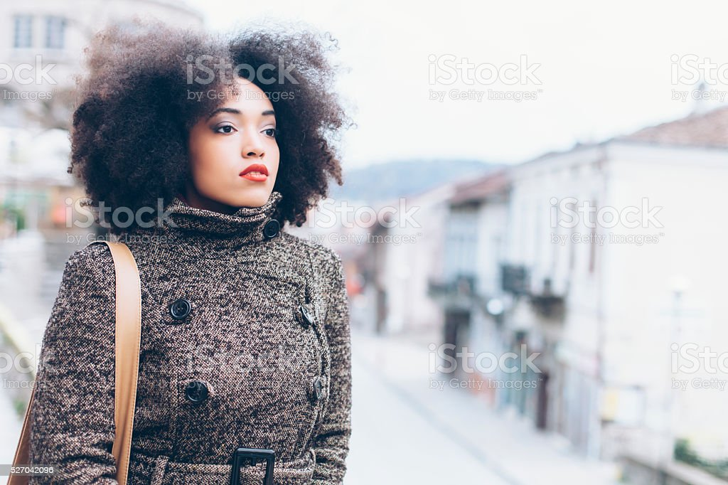 Portrait of pensive young woman on street stock photo