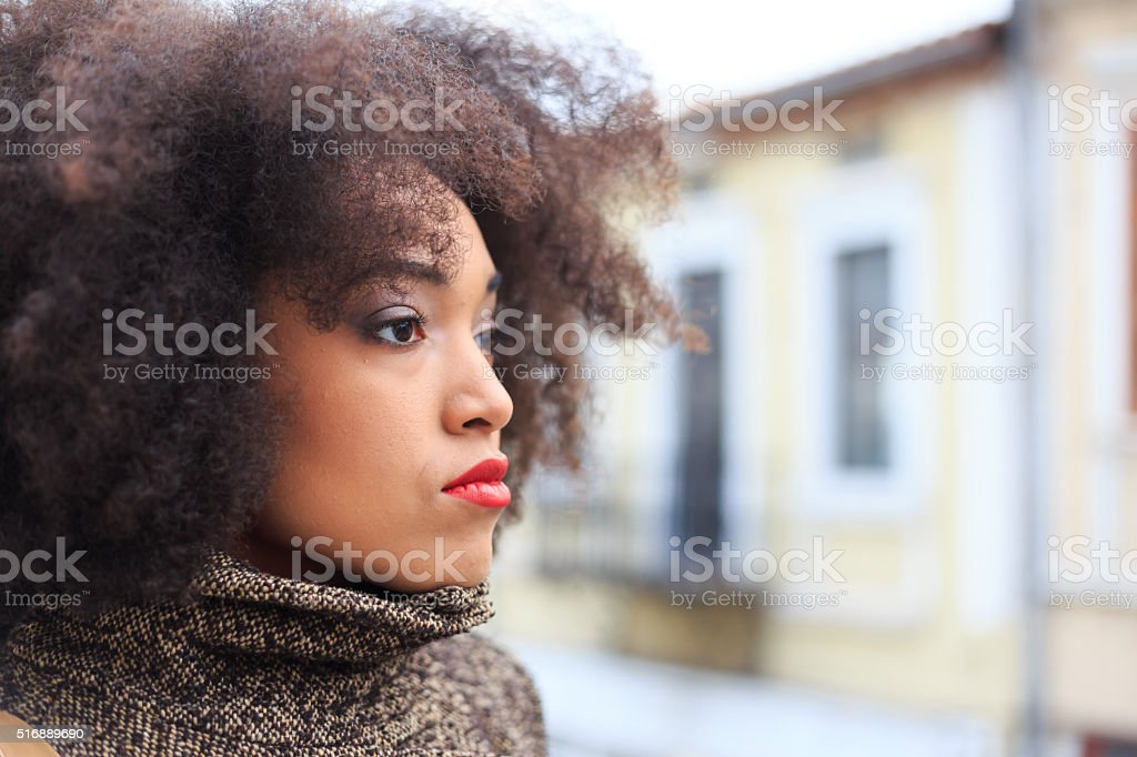 Portrait of pensive young woman on street-side view stock photo