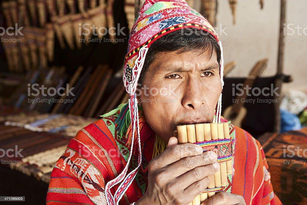 Portrait of Peruvian man playing a siku (panpipe), Pisac market stock photo