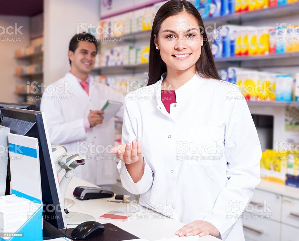 Portrait of pharmacist and assistant working stock photo