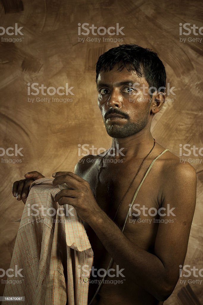Portrait of poor man with bare torso holding ragged shirt royalty-free stock photo
