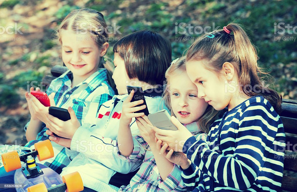 Portrait of positive kids playing with phones stock photo