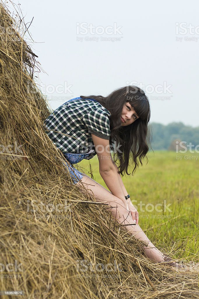 Portrait of pretty brunette lying on haystack royalty-free stock photo