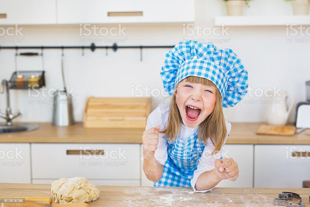 Portrait of pretty little girl funny screams a kitchen stock photo