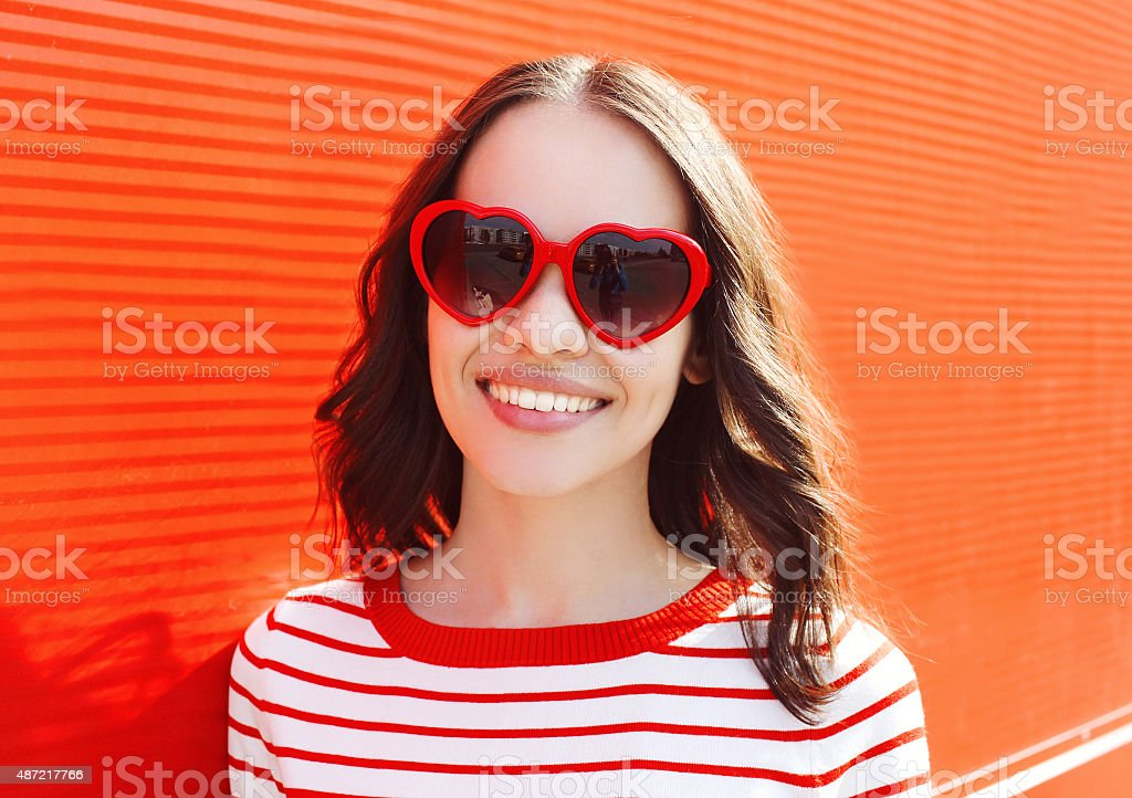 Portrait of pretty smiling woman in red sunglasses outdoors stock photo