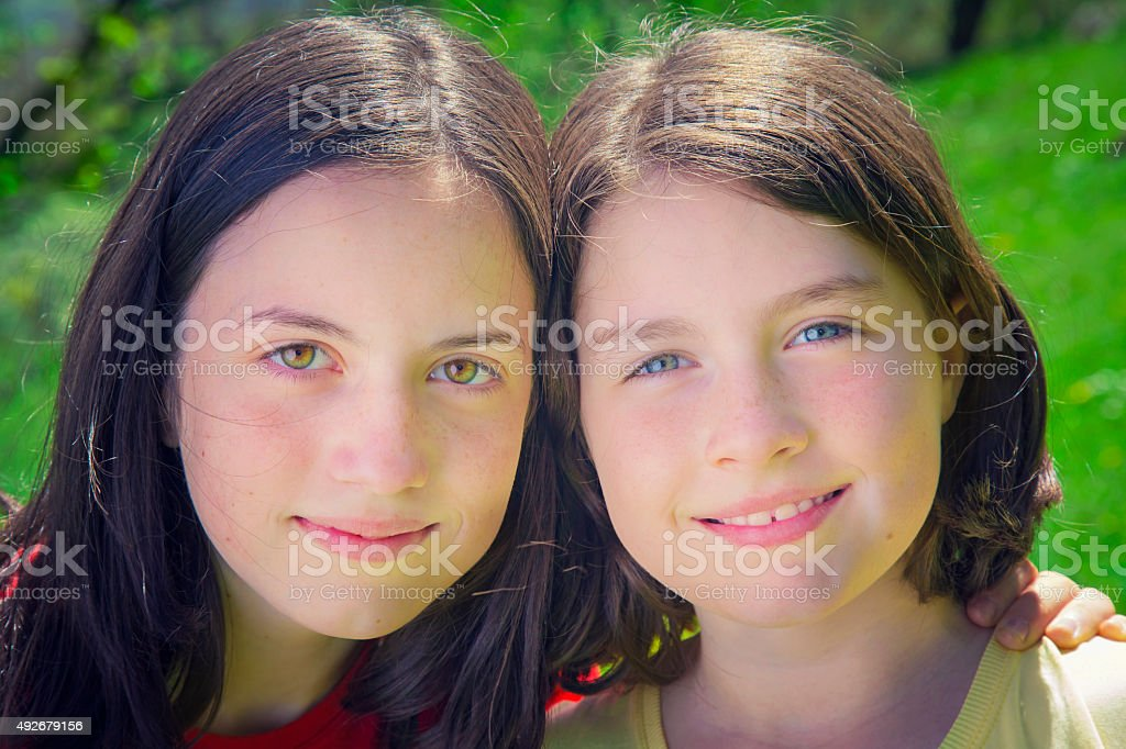 Portrait of pretty teenage sisters smiling royalty-free stock photo