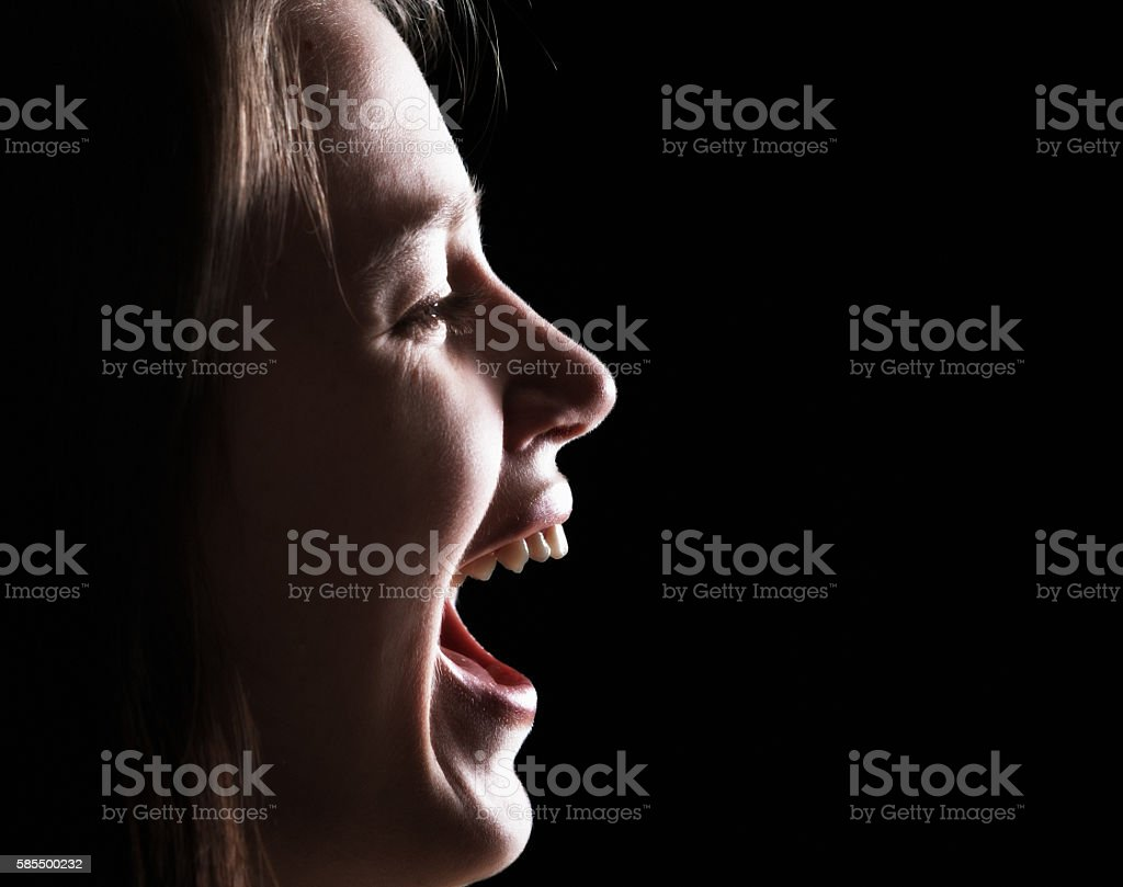 Portrait of pretty young woman laughing in profile on black stock photo